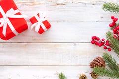 Caixa de presentes do presente de Natal e elementos vermelhos da decoração no fundo de madeira branco Imagem de Stock