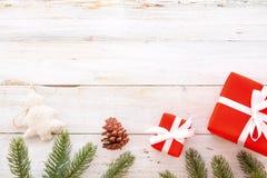 Caixa de presentes do presente de Natal e elementos vermelhos da decoração no fundo de madeira branco Fotos de Stock Royalty Free