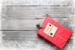 Caixa de presentes vermelha do presente de Natal no fundo de madeira do vintage com floco de neve Foto de Stock Royalty Free