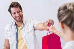 Caixa de sorriso que dá o saco de compras à mulher fotos de stock royalty free