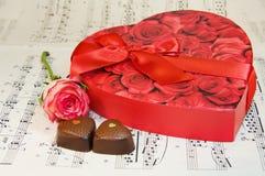 A caixa do coração dos chocolates com levantou-se sobre notas da música fotografia de stock royalty free