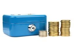 Caixa do dinheiro com fechamento e as moedas empilhadas Fotografia de Stock Royalty Free