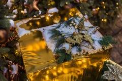 Caixa do ouro do Natal com presentes Bolas douradas e festão iluminada com lanternas elétricas imagens de stock