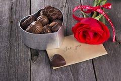 Caixa dos chocolates, rosa do vermelho em um fundo escuro Imagens de Stock Royalty Free