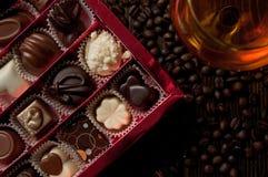 Caixa dos confeitos belgas do chocolate cercados por feijões de café e Imagens de Stock Royalty Free
