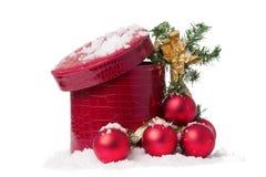 Caixa e baubles vermelhos na neve isolada Imagens de Stock