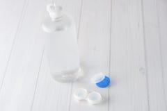 Caixa e solução de lentes do contato no fundo branco imagens de stock