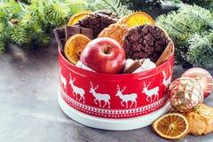 A caixa festiva do frasco do Natal com a laranja vermelha das cookies do Natal das barras de chocolate da maçã lasca a caixa de p imagens de stock royalty free