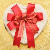 Caixa Heart-shaped com curva em um fundo do ouro imagem de stock royalty free