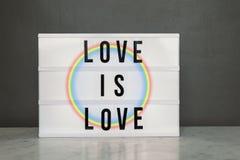 A caixa leve com amor do ` é ` e arco-íris do amor Imagem de Stock Royalty Free