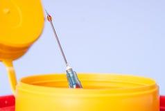 Caixa médica amarela do desperdício da eliminação, agulha da seringa com gota vermelha na ponta Foto de Stock