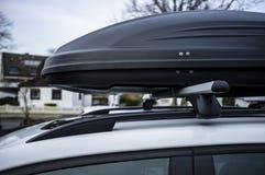 Caixa montada Closed do tronco ou da carga no telhado do carro, antes de uma viagem das férias em família, contra um céu azul, ár imagem de stock