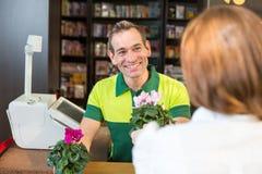 Caixa no cliente do serviço do florista imagem de stock