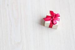 Caixa para anéis com uma fita vermelha na tabela Imagem de Stock Royalty Free