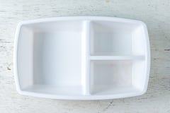 Caixa plástica branca para o alimento no fundo de madeira Fotografia de Stock