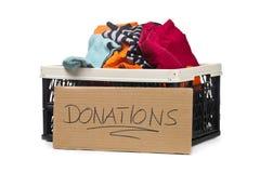 A caixa plástica com doações da roupa e o cartão assinam imagens de stock royalty free