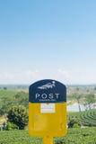 Caixa postal amarela no campo do chá com céu Imagem de Stock Royalty Free