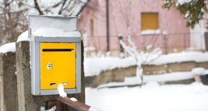 Caixa postal coberto de neve na frente de uma casa Imagem de Stock