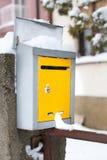 Caixa postal coberto de neve na frente de uma casa Foto de Stock