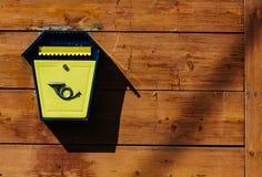 Caixa postal do metal amarelo em uma parede de madeira Foto de Stock