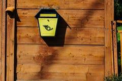 Caixa postal do metal amarelo em uma parede de madeira Imagem de Stock