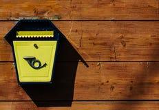 Caixa postal do metal amarelo em uma parede de madeira Fotos de Stock