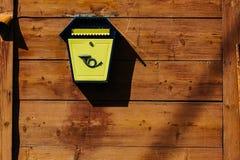 Caixa postal do metal amarelo em uma parede de madeira Imagens de Stock
