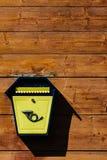 Caixa postal do metal amarelo em uma parede de madeira Imagens de Stock Royalty Free