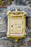 Caixa postal francesa amarela na parede de pedra Fotografia de Stock