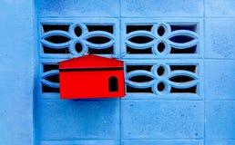 Caixa postal vermelha na casa azul da parede Foto de Stock