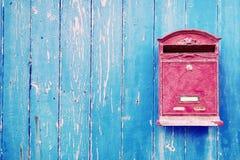 Caixa postal vermelha na porta de madeira azul Imagens de Stock Royalty Free