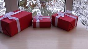 Caixa três do presente na tabela na frente da janela no inverno filme