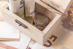 Caixa velha de madeira com as euro- moedas e c?dulas imagens de stock
