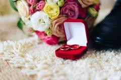 Caixa vermelha com alianças de casamento do ouro, sapatas do ` s do noivo e ramalhete do casamento Imagem de Stock Royalty Free