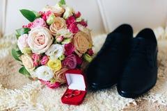 Caixa vermelha com alianças de casamento do ouro, sapatas do ` s do noivo e ramalhete do casamento Fotografia de Stock Royalty Free
