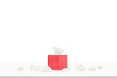 Caixa vermelha com tecidos de papel em uma tabela Fotos de Stock