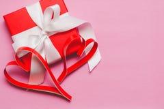 Caixa vermelha com um presente, amarrado com uma fita branca, e corações de papel caseiros vermelhos em um fundo cor-de-rosa Símb foto de stock royalty free