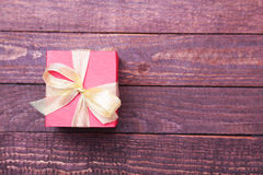 Caixa vermelha do presente do Natal com a curva da cor do ouro isolada no fundo branco Foto de Stock Royalty Free