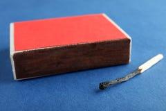 Caixa vermelha e fósforo queimado no fundo da cor imagens de stock