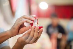 Caixa vermelha a mostrar, aliança de casamento da posse da mão do ` s do noivo Símbolos do casamento e da união fotos de stock royalty free