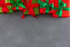 Caixas atuais no papel da cor no fundo cinzento para xmas, ano novo Foto de Stock