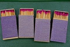 Caixas azuis completamente dos fósforos em uma tabela verde foto de stock
