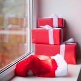 Caixas com os presentes do Natal e o chapéu de Santa que encontram-se na janela Fotografia de Stock Royalty Free