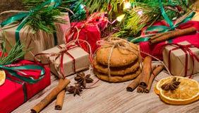 Caixas com presentes, cookies do pão-de-espécie sob o pinho do Natal Fotografia de Stock Royalty Free
