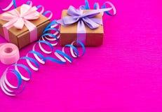 Caixas com presentes em um fundo cor-de-rosa brilhante Imagem de Stock