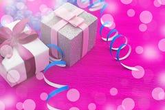 Caixas com presentes em um fundo cor-de-rosa brilhante Imagens de Stock