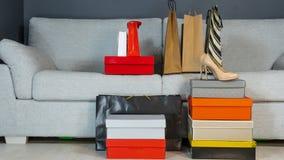 Caixas com sapatas e sacos de compras no fundo de um sofá cinzento imagem de stock