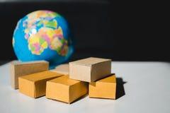 Caixas de cartão da pilha com mini fundo do globo fotografia de stock