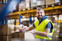 Caixas de cartão masculinas da selagem do trabalhador do armazém imagens de stock