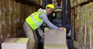 Caixas de embalagem do trabalhador do armazém na empilhadeira filme